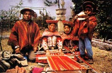 A weaving family of Chincheros, Peru. The loom is warped to weave a poncho.